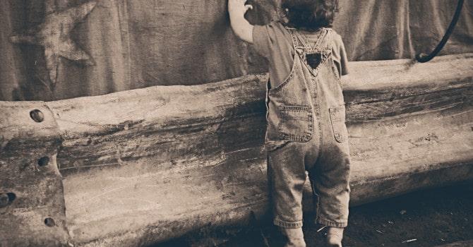 Kleines Kind hält sich an einer Wand fest